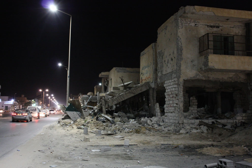 Buildings in rubble at night