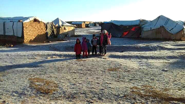 A family poses after snow for a mobile phone photo at the Jordan-Syria berm zone at the border
