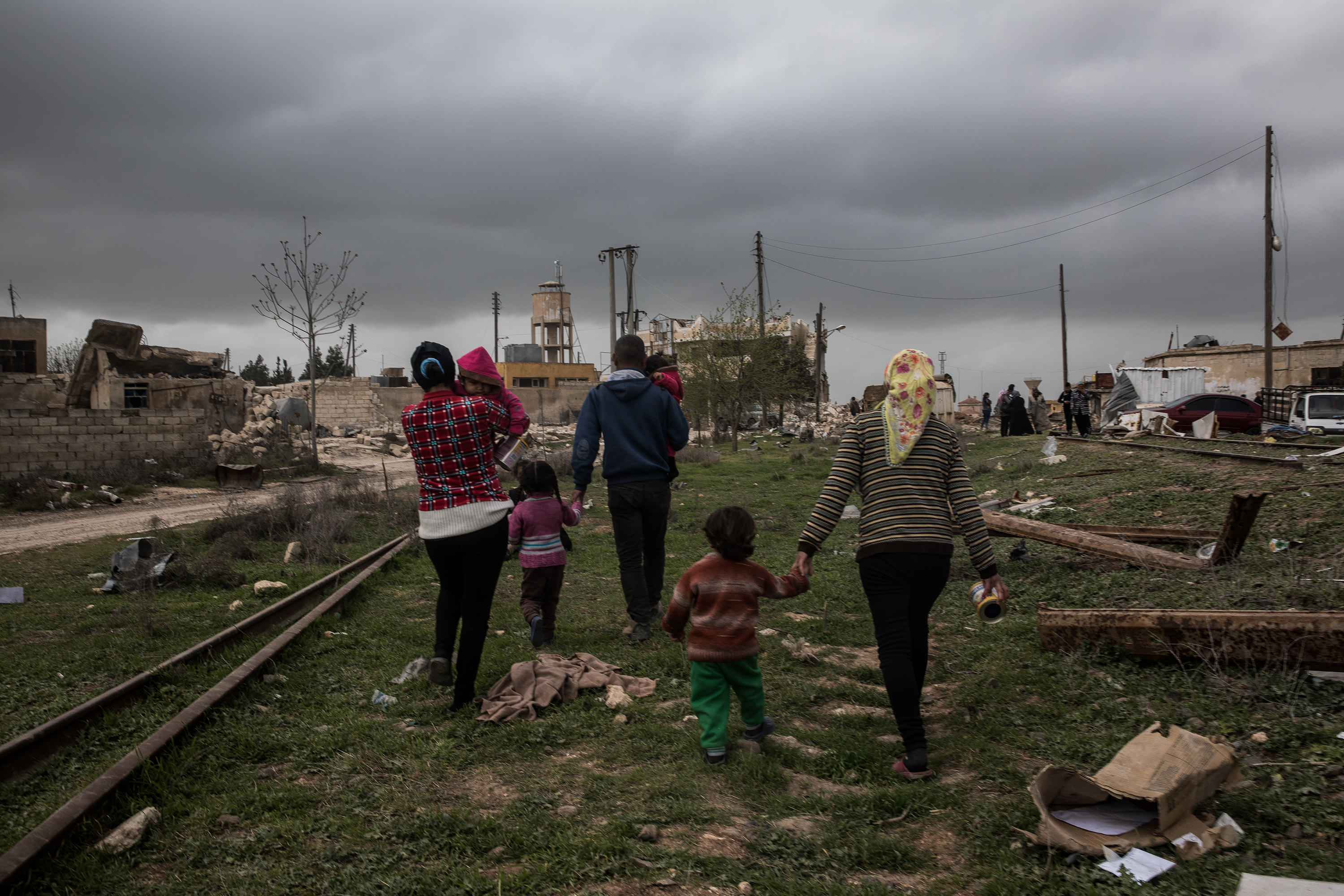 A family walks away from the camera through a destroyed town