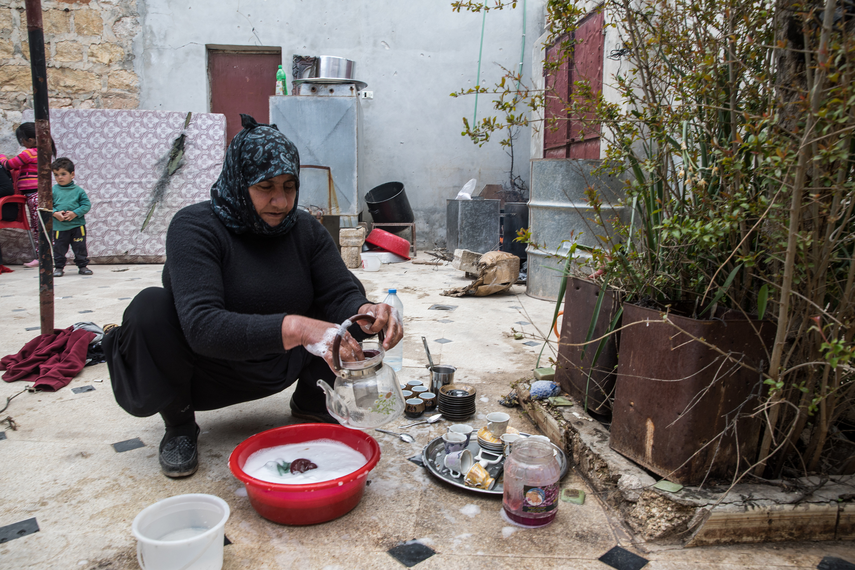 A woman washes dishes inside the remnant of a building with a makeshift home around her