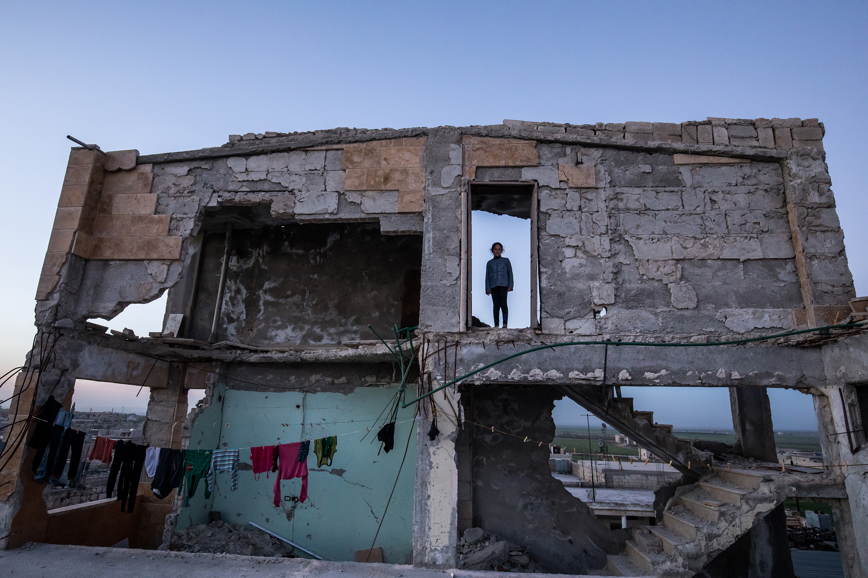 An exterior face of a destroyed building with the silhouette of a young girl in an open doorway on the second floor