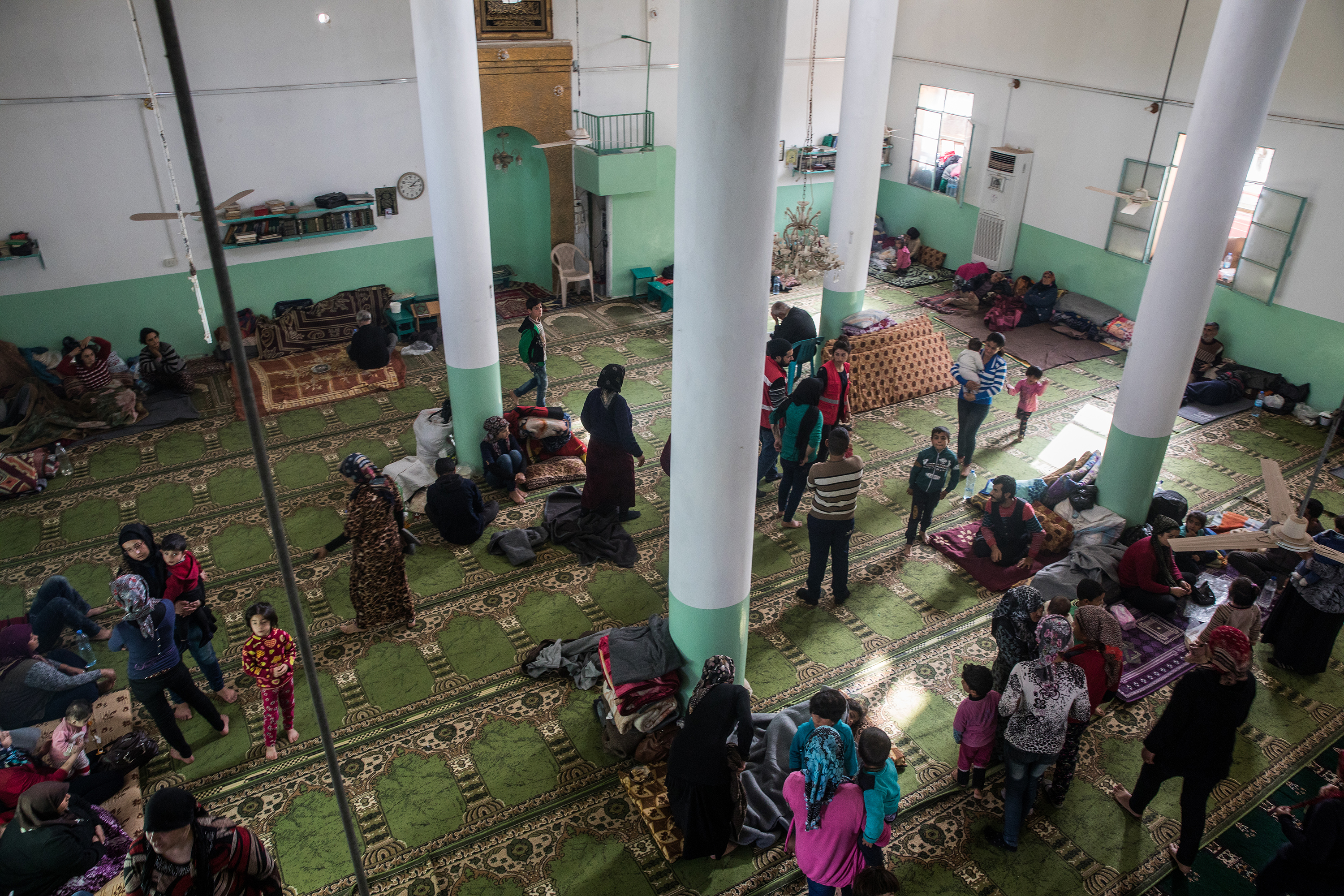 An overhead shot of many families set up inside the open mosque floor. The carpet is green with a decorative pattern.