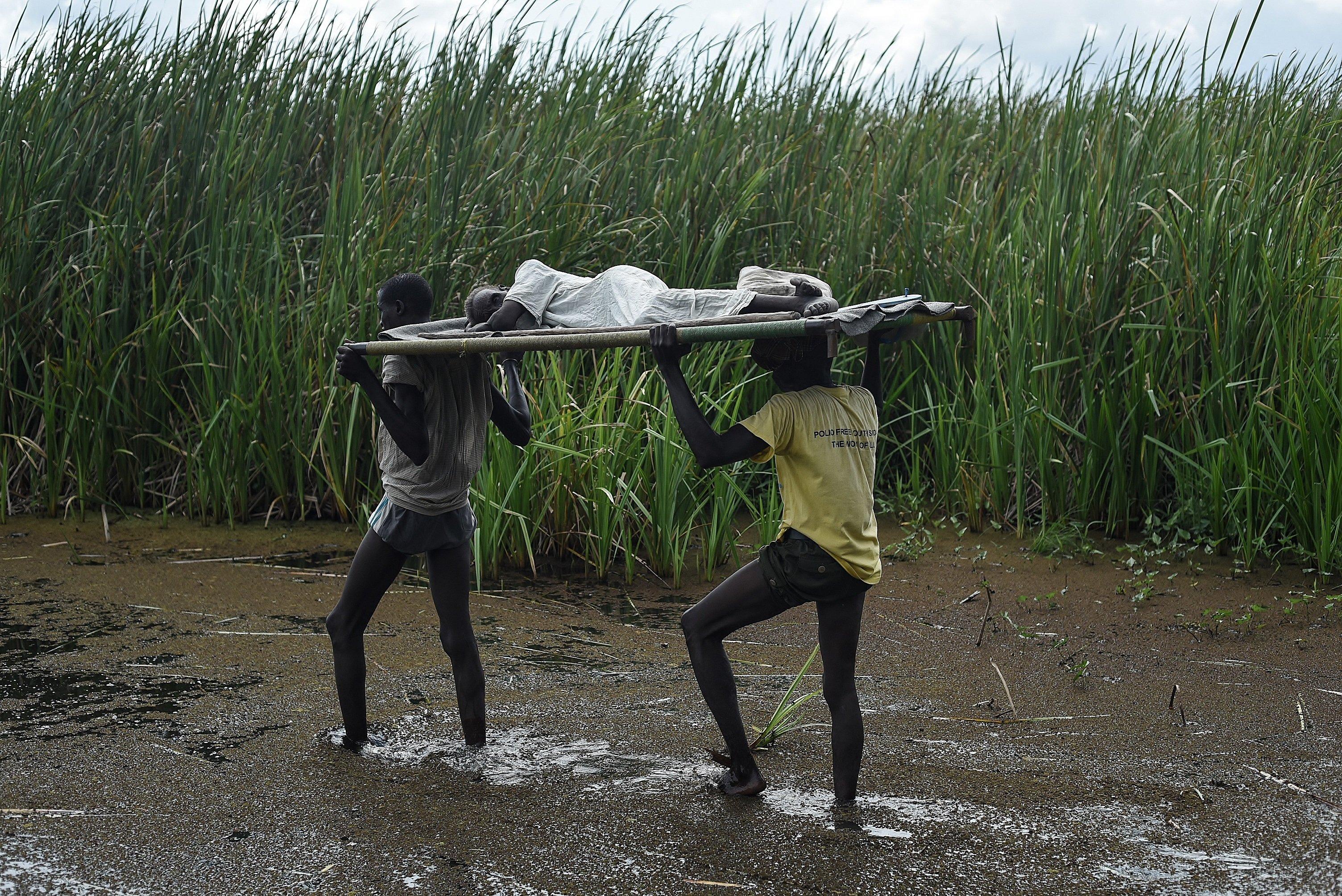 Men carry an elderly woman through the swamps