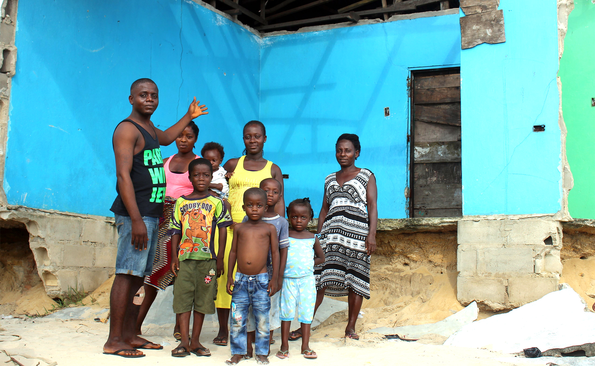 A family in front of a broken building