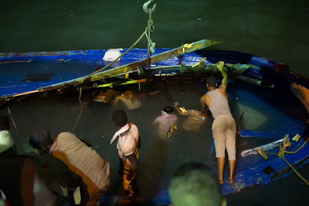 Volunteers remove trapped bodies of migrants from a capsized boat