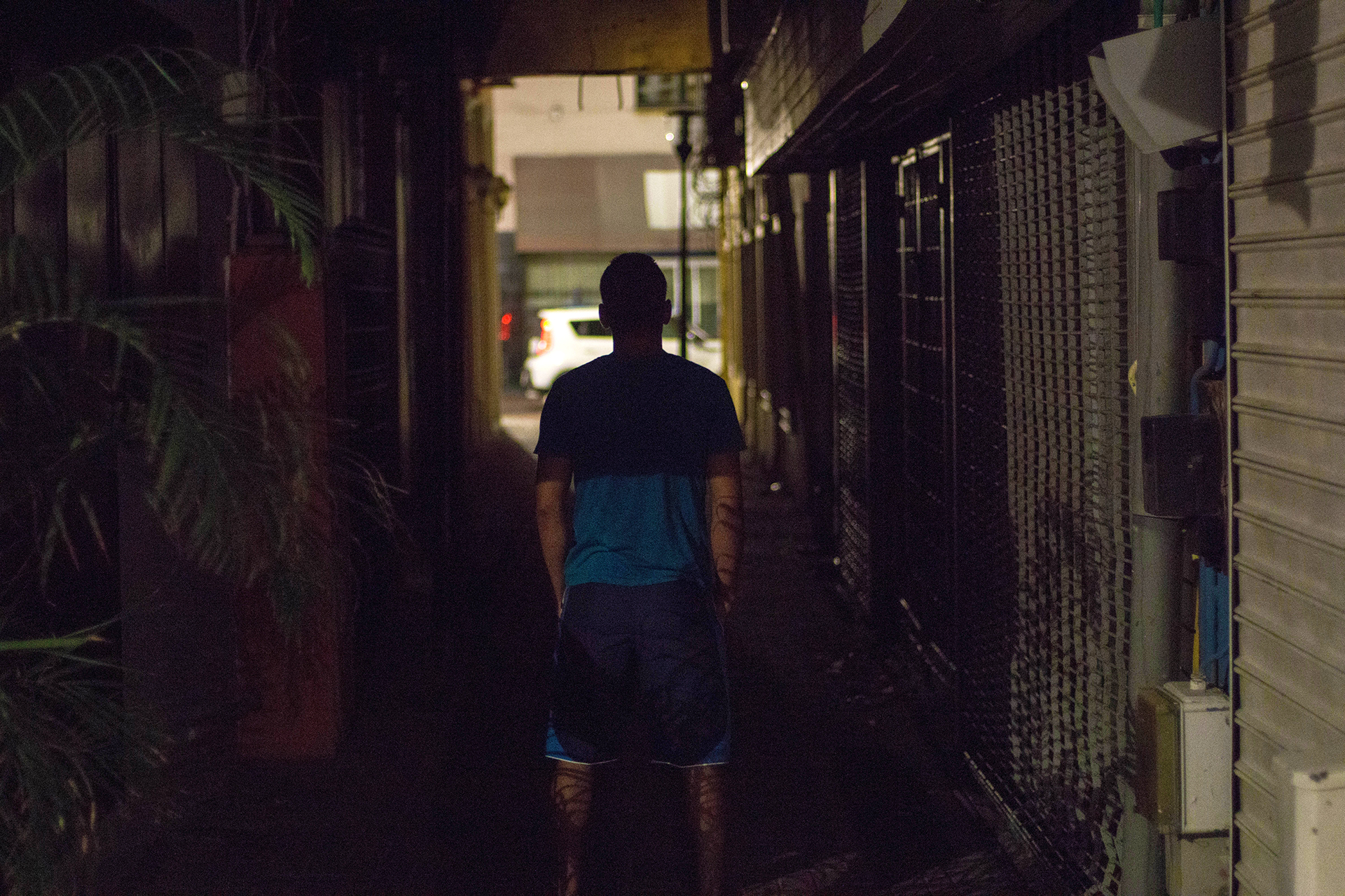 A silhouette of a man facing away in a dark alley.