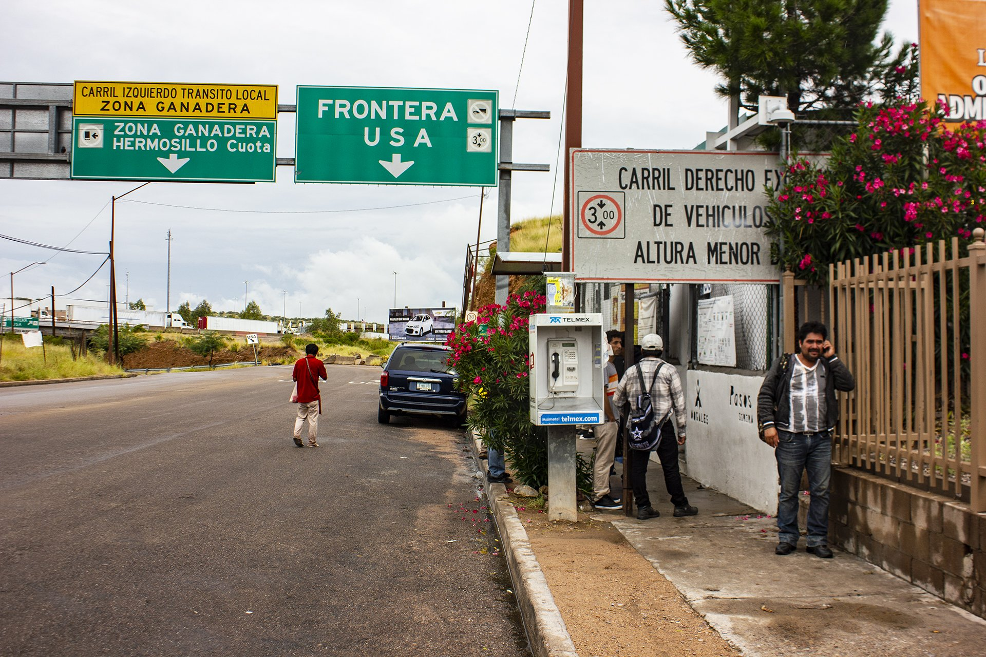 People on a street with a highway sign pointing to the border.