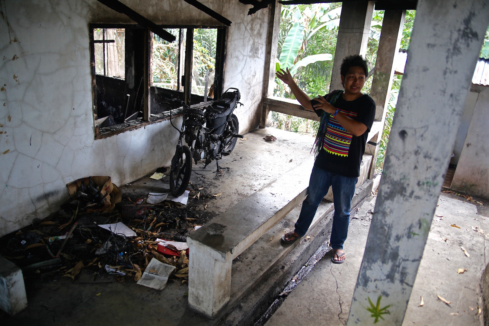 Rius Valle shows a firebombed building at the church sheltering displaced indigenous people in Davao City