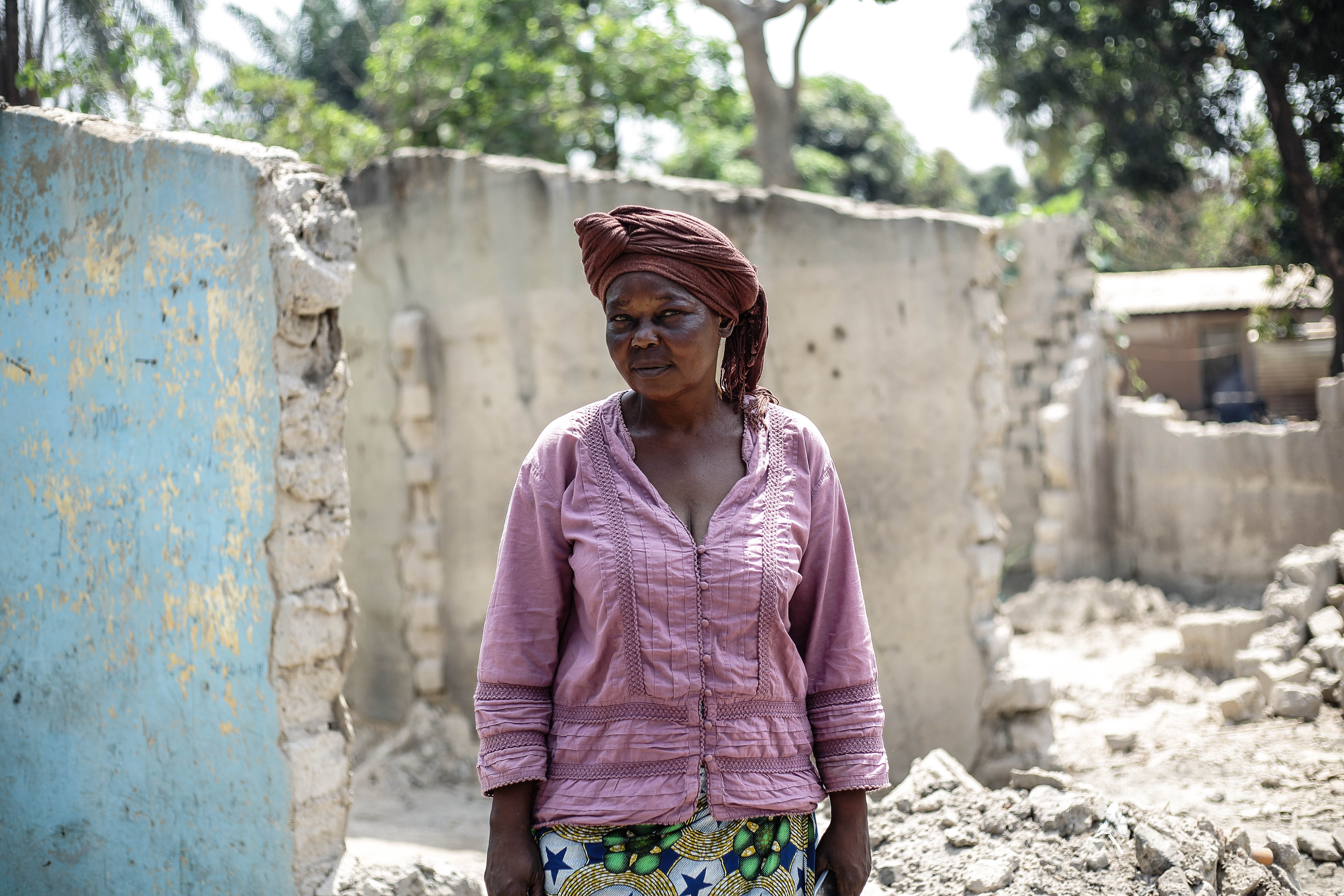 Melanie Ouagram stands outside her destroyed home in Fondo
