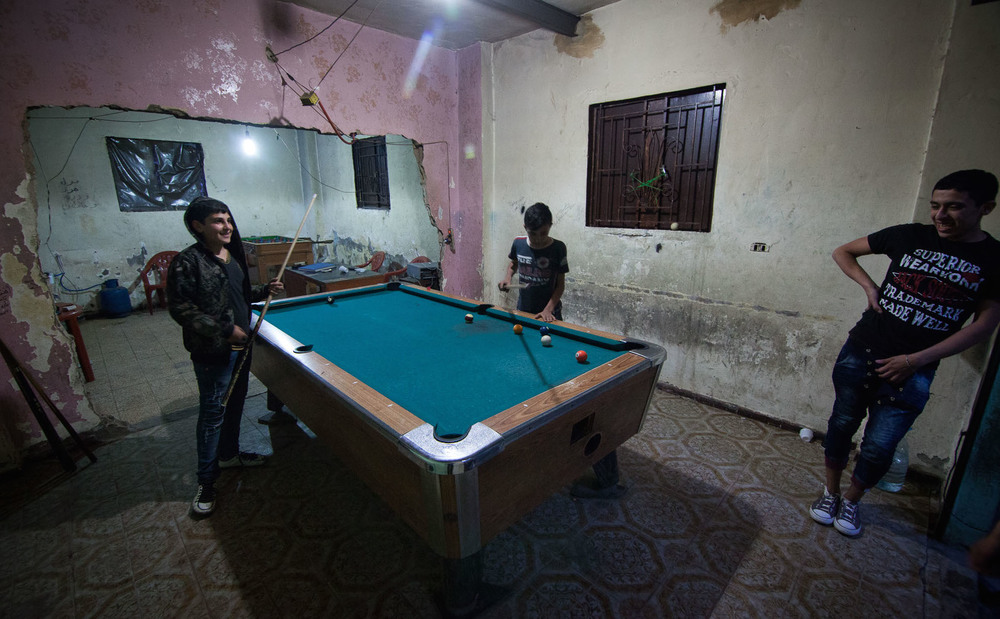 Three smiling young people playing pool