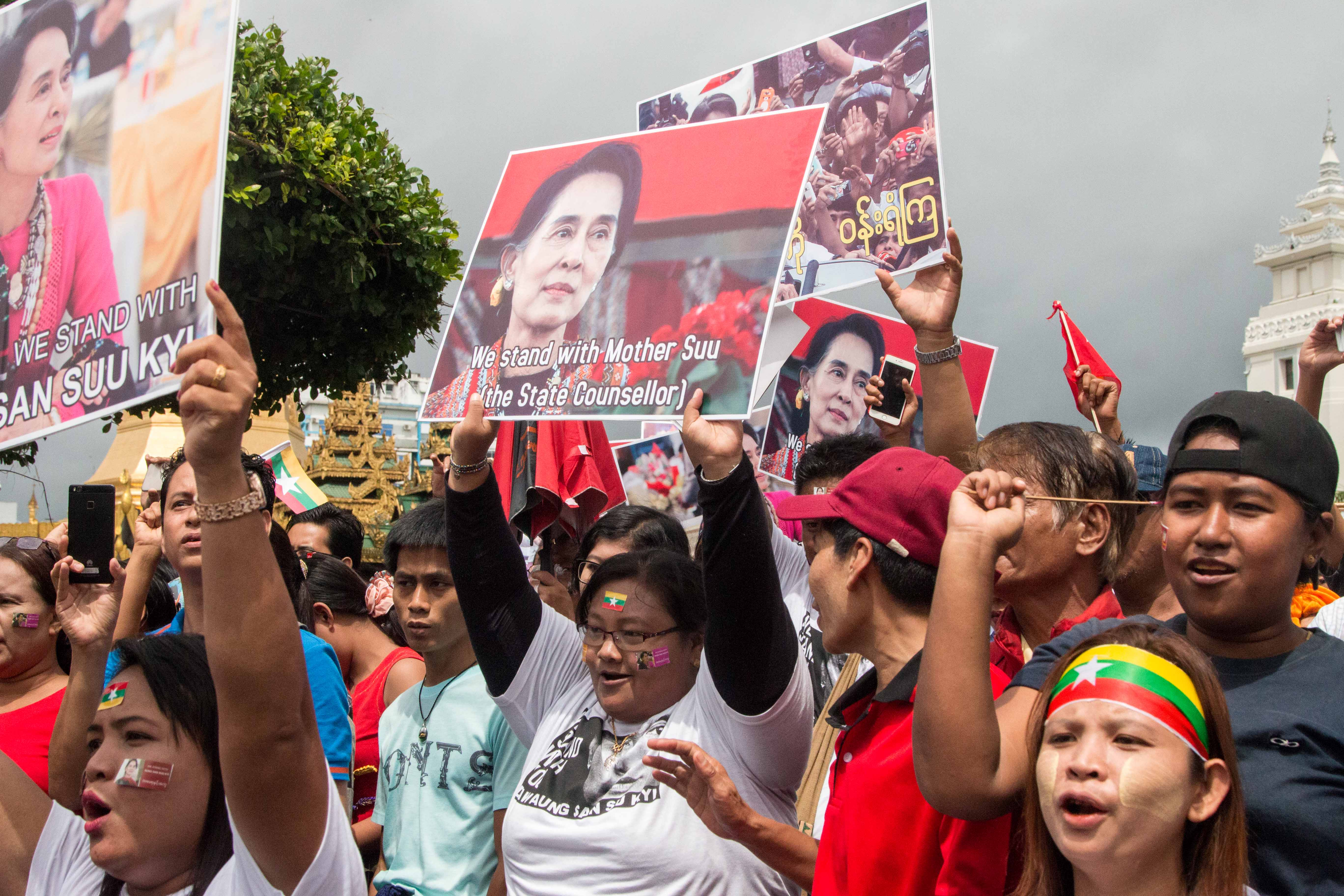 People hold signs supporting Aung San Suu Kyi