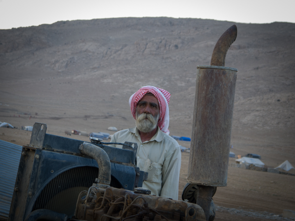 A Yazidi man guards a water well on top of Mount Sinjar