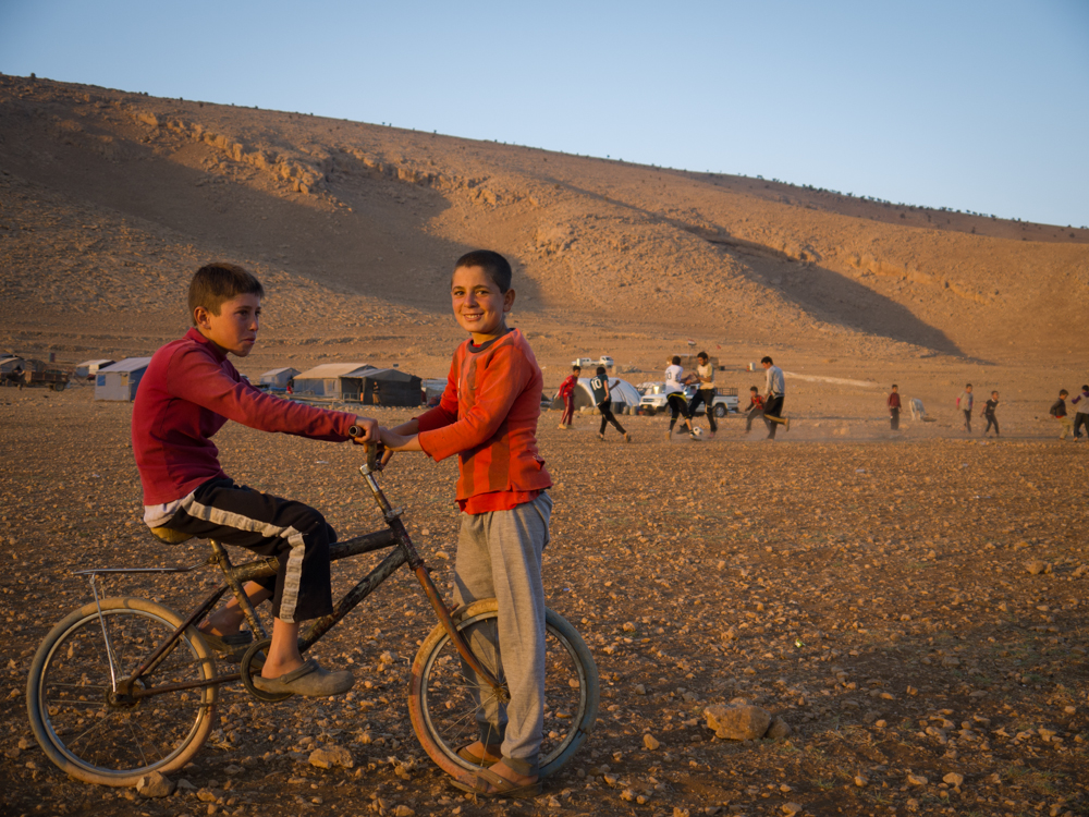 Children play on top of Mount Sinjar as the sun sets