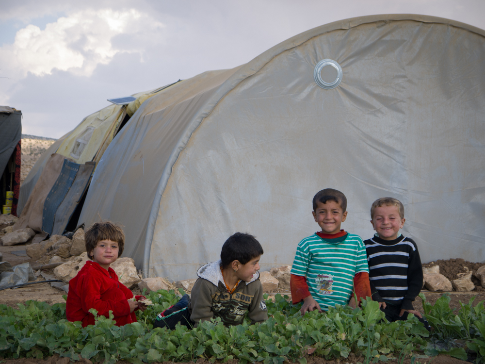 Yazidi children in front of a small garden on top of Mount Sinjar