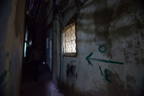 A dark corridor where a barely visible man uses a keyring light to help navigate in Beirut, Lebanon.
