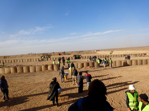 A system of barriers for security screening dominates an aid distribution point at the berm between Jordan and Syria