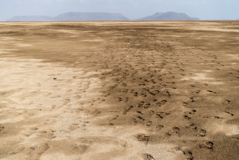 A trail of human footprints that stretches into the horizon marks the spot where hundreds of migrants walk, across the dry desert planes from Obock to Gahere Beach