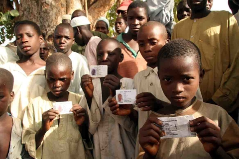 Underage voters brandish their voter registration cards while waiting to cast their ballots in presidential elections at a rural polling station in Jigawa State, northern Nigeria, 21 April 2007. Despite looking not more than ten years old, their voter reg