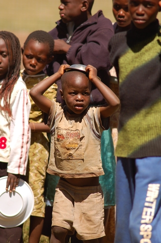An internally displaced child lines up to get food aid at the Thika stadium, Kenya. Many people have been displaced as a result of the post election violence.