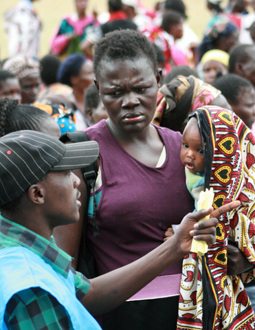 A displaced woman listens to a volunteer (left) during the distribution of clothes donated to IDPs at the Nairobi Showground camp for the internally displaced on 13 February 2008.