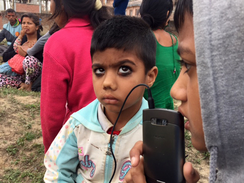 Children living in a temporary camp listen to the radio on a smart phone after being displaced by a 7.8 magnitude earthquake that struck Nepal 25 April 2015