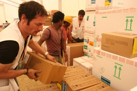 Olivier Brandner, left, loads supplies in Medecins Sans Frontieres' (MSF) mobile storage unit at the Humanitarian Forwarding Area in the Nepalese capital Kathmandu on 1 May 2015, after a 7.8-magnitude hit the country.