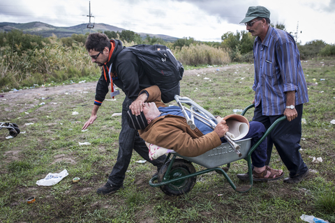 Aid worker, Pane Ignov helps pull Syrian refugee, Bashar, who lost his leg to diabetes, through the no man's land between Macedonia and Serbia