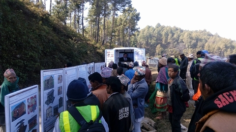"Nepalis receive information in late 2015 about safely rebuilding homes destroyed by the April 2015 earthquake via a ""mobile video van"" provided by the United Nations Development Program."