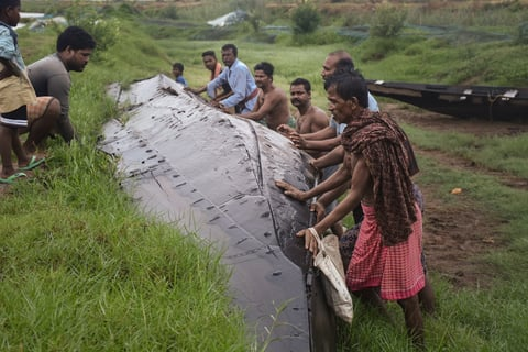 Photo of fishermen overturning a boat in a canal in India after Cyclone Fani.
