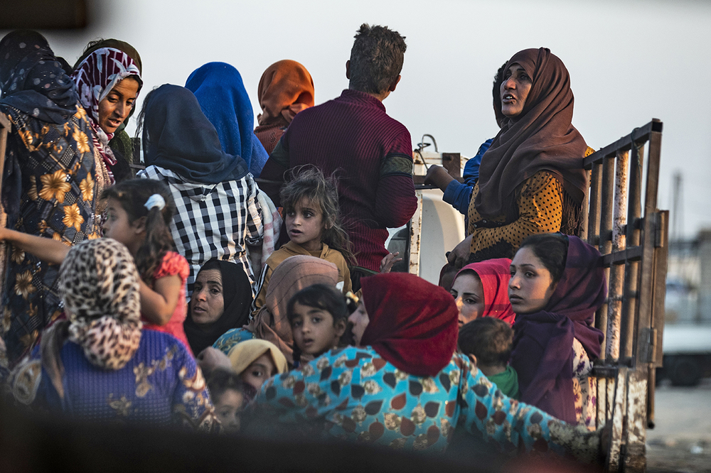 Syrian Arab and Kurdish civilians flee amid Turkish bombardment on Syria's northeastern town of Ras al-Ain in the Hasakeh province along the Turkish border on 9 October 2019.