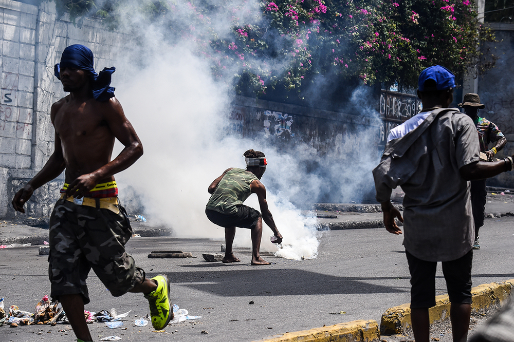 A demonstrator douses a tear gas canister with water during a protest in Port-au-Prince, Haiti, on 27 September 27, 2019.