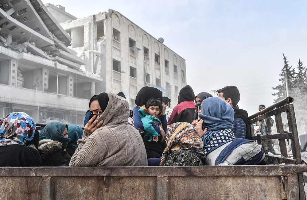 AFP Photo Civilians sit in the back of a truck as they flee the city of Afrin in northern Syria on March 18, 2018