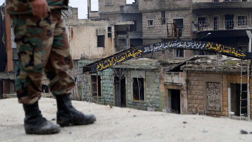 A Syrian army soldier stands on a roof near a street sign that was written by rebels in the streets of Maarat al-Numan, the town taken this week by government forces.