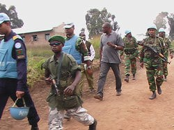 [DRC] Germain Molondo, the director of the DRC's Committee for Disarmament, Demobilisation, and Reintegration (CONADER), in grey shirt, and UN troops escort a child soldier to the Aveba transit camp for cantonement and demobilisation