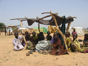 [Chad] Refugee children from Darfur wile away the hours under makeshift shelters in Bredjing refugee camp, eastern Chad. September 2004.