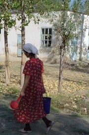 [Kyrgyzstan] A female resident in Barak enclave surrounded by Uzbek territory is carrying water home.