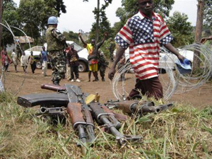 [DRC] A former child soldier walks past guns handed in by ex-combatants before entry into a disarmament centre in Kpandroma, Ituri District. February 2005.