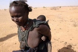 [Niger] A Nigerien slave arrives at the traditional well with a young slave on her back, to collect water for their master. The specific form of slavery found in Niger, is descent-based slavery where a slave class exists that people are born into.  They a