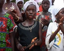 [Sierra Leone] A girl with the knife in her hands in an initiation ceremony. She will be taught to became a 'sowie' assistant. The custom provides an income to the women who perform the circumcisions.