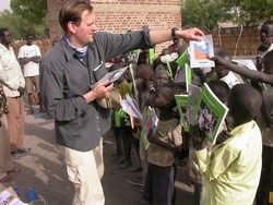 [Sudan] Klaus Stieglitz of German NGO Sign of Hope distributes books to children in Old Fangak, southern Sudan.