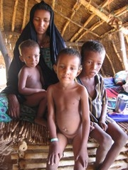 [Mali] A young women with her three children, one of which wears the green bracelet to show he is malnourished - Marsi, August 2005.