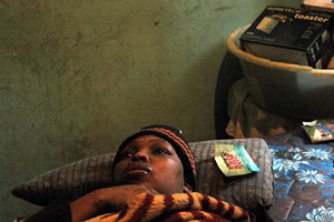 Twana Dlamini, a person living with HIV/AIDS, lies helpless in bed. The nearest government hospital where she can access treatment is 70 km away, 4 July 2006, Swaziland. About a third of all adults in Swaziland are infected with HIV. Thousands of children