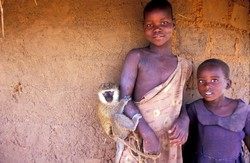 [Uganda] Two girls pose with their pet monkey at Cet Kana, a decongestion camp for internally displaced persons (IDPs) in Gulu District, northern Uganda, August 2006.  Almost half of the approximately two million IDPs in Uganda are children.