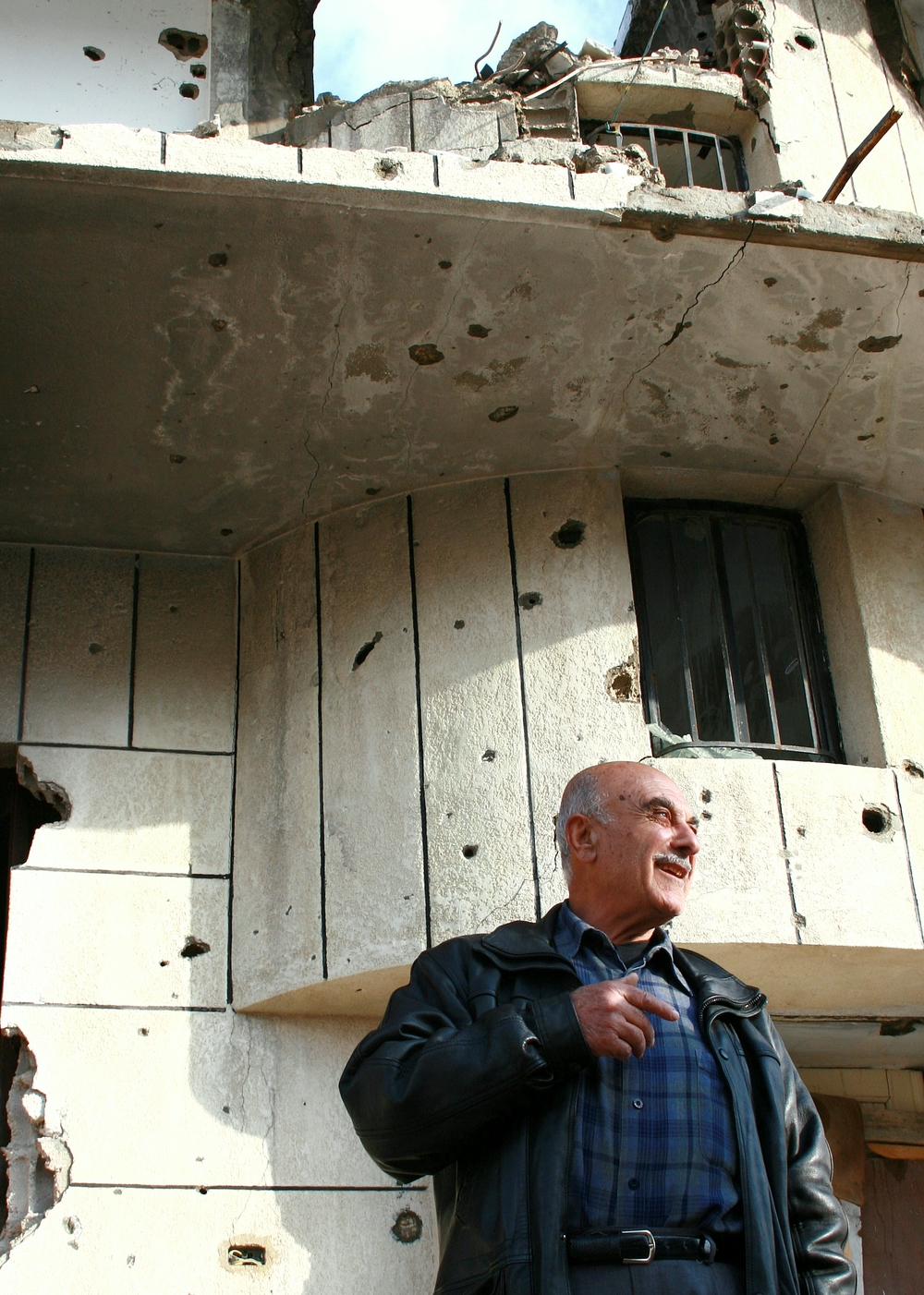 Khalil Ajami stands by the ruins of his four-apartment family home in Bint Jbeil.