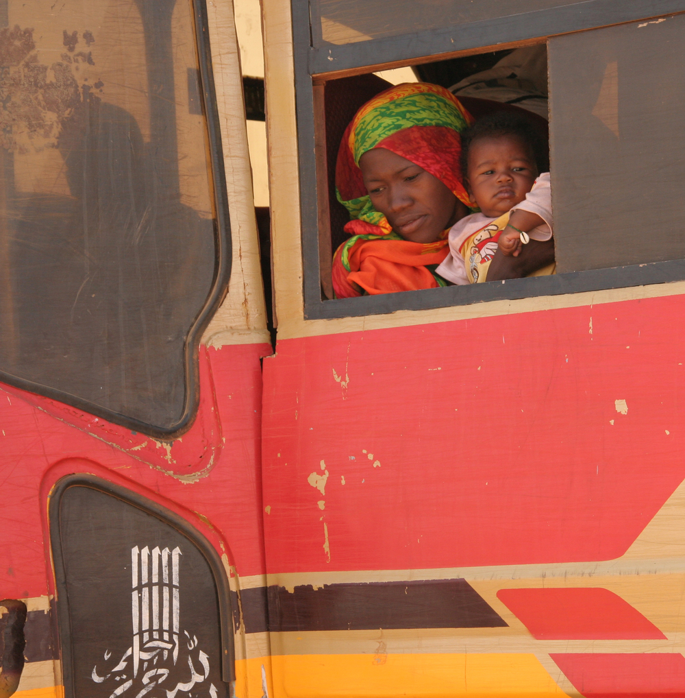 A returnee woman and her baby in Khartoum peep through the window of a bus taking them back to their home of origin in Southern Kordofan State, Sudan, 16 May 2007.