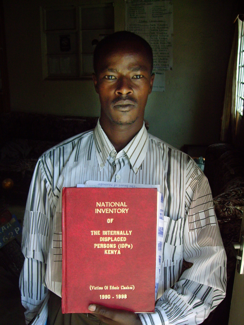 Keffah Magenyi, , National Coordinator of the IDP Network, holding the large National Inventory of IDPs in Kenya for 1990 to 1998 during the interview in Molo, Kenya, 9 July 2007.
