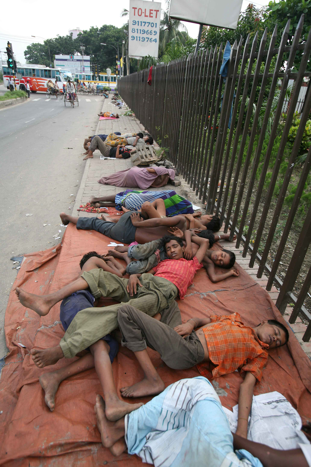 Street children sleep on the path of one of Dhaka's roads, Bangladesh, July 2007. The country is one of the poorest in the world. A large percentage of the population is young and living below the poverty level.