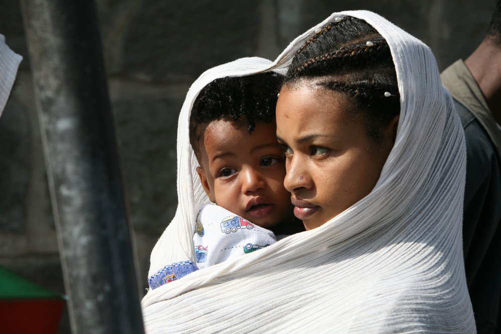Mother and child arrive at a Christian Orthodox church in Addis Ababa, Ethiopia, May 2007. To preserve the ancient prayer tradition, the young are involved in a number of activities within the church.