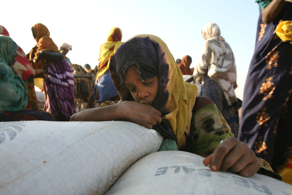 A girl relaxes on the sacks of maize at the food distribution in Jowhar, Somalia, September 2007. Up to 1.5 million of Somalia's estimated seven million people need food aid. Nearly 300,000 face severe food shortages in the Horn of Africa nation.
