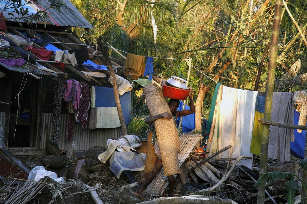 A man transfers his belongings two days after Cyclone Sidr struck his home. Thousands of people along (Bagerhat district) southern Bangladesh's, November 2007, were killed, with many more injured.